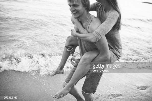 man carrying girlfriend on his back at summer beach. young couple enjoying holidays at the seashore. - marriage stock pictures, royalty-free photos & images