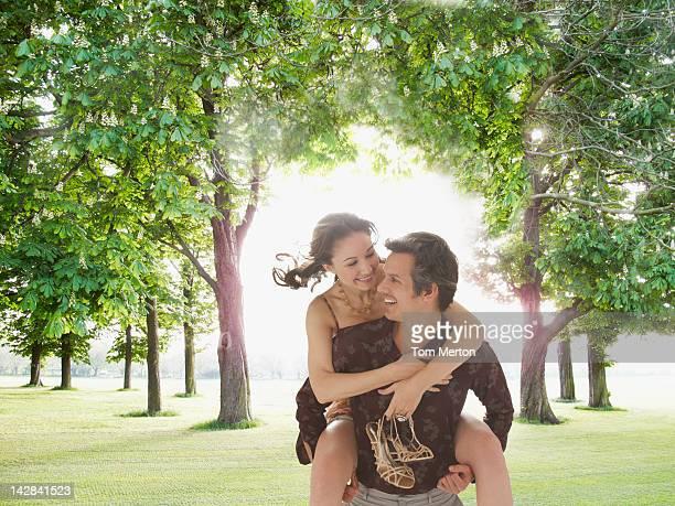 Man carrying girlfriend piggyback in field
