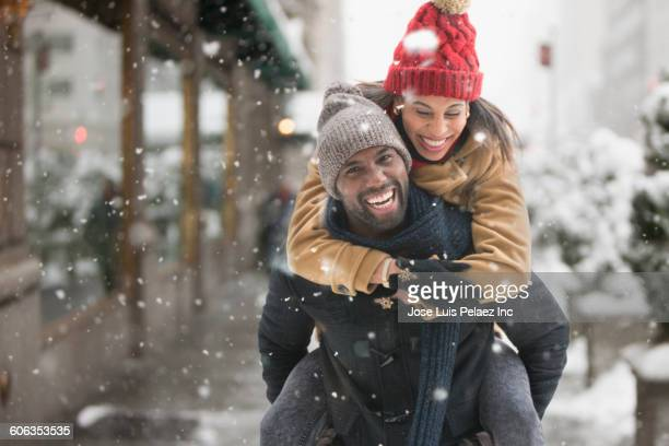 Man carrying girlfriend piggyback in snow