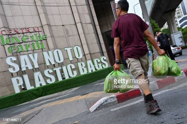 TOPSHOT A man carrying goods in plastic bags crosses a street where a sign promoting a plastic bagfree shopping experience is displayed outside a...