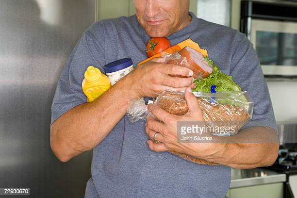 Man carrying groceries in kitchen, mid section