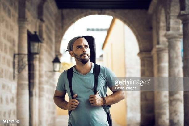 man carrying guitar case while walking in corridor - guitar case stock pictures, royalty-free photos & images