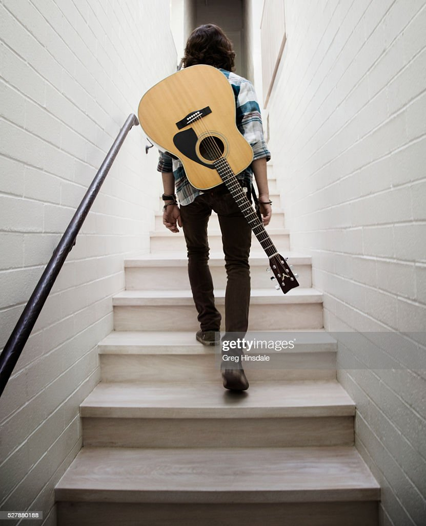 Man Carrying Guitar On Shoulders Stock Photo