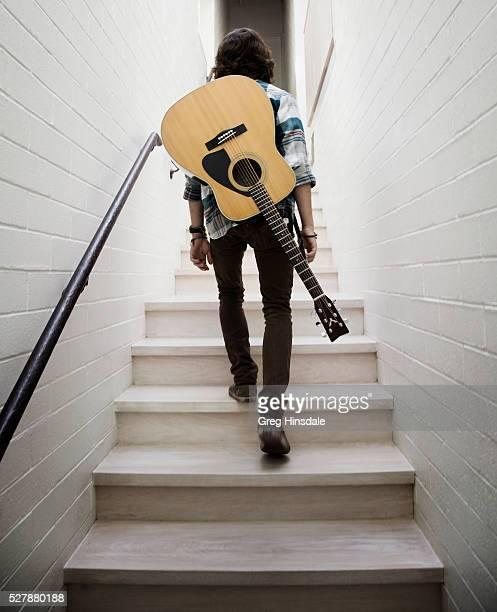 man carrying guitar on shoulders - guitariste photos et images de collection