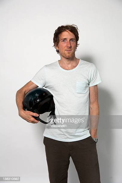Man carrying helmet against white background