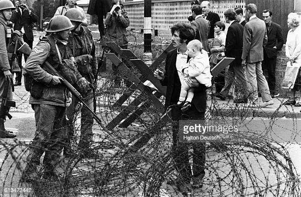 A man carrying his baby approaches a barricaded point on the Falls Road in Belfast which is guarded by British soldiers