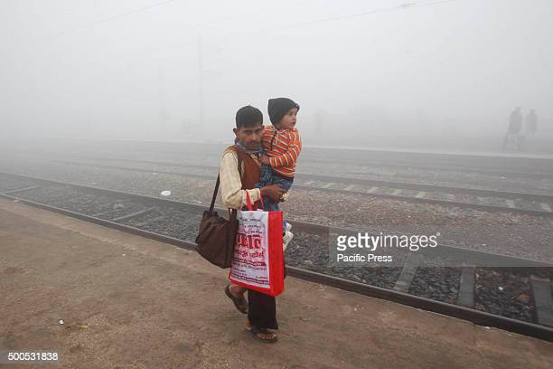 A man carrying his child as he walks on railway platform on a foggy morning at Phaphamau railway station