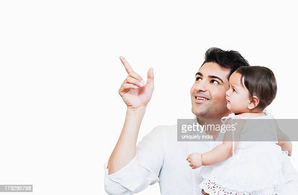 Man carrying his daughter and pointing away with finger