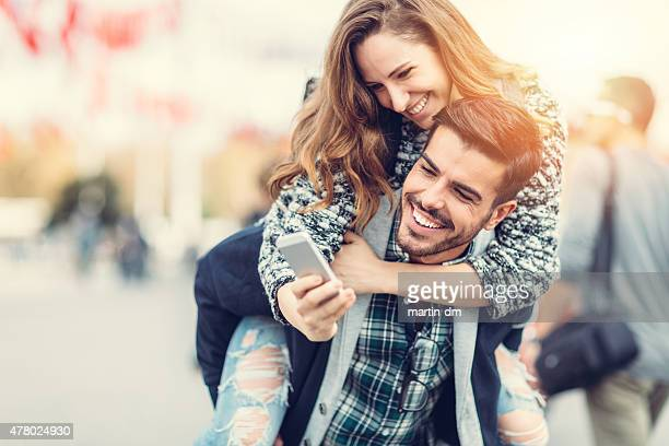 Mann mit seiner Freundin Huckepack nehmen selfie am für