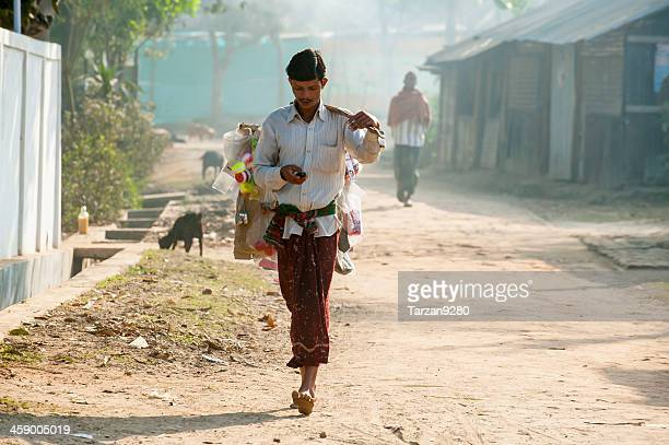 man carrying his goods walking in small village - bangladesh village stock photos and pictures