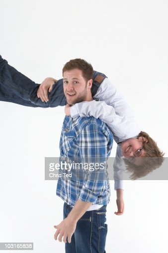 man carrying his little brother over his shoulder stock photo