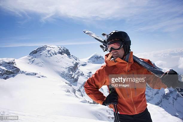 Hombre de transporte de sus esquís en las montañas