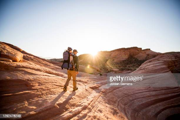 a man carrying his son in a backpack while hiking in the red rocky desert landscape. - nevada stock-fotos und bilder