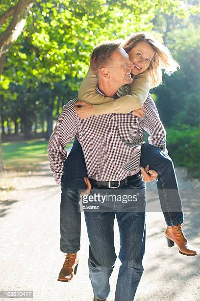 Man carrying his wife on piggy back