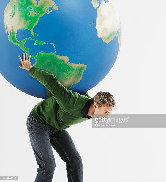 Man carrying huge globe on back against white background