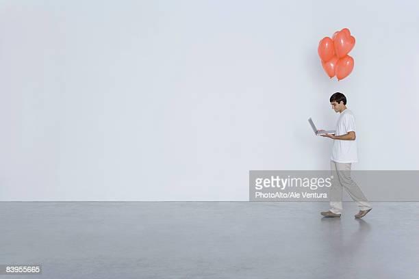 man carrying laptop computer and heart balloons, side view - vrijgezel stockfoto's en -beelden