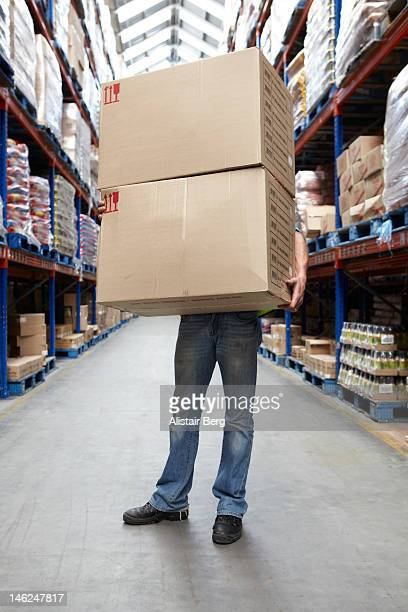 Man carrying large boxes in warehouse