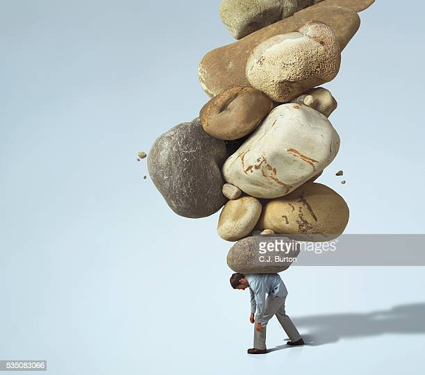 man carrying large rocks on his back - burden stock pictures, royalty-free photos & images