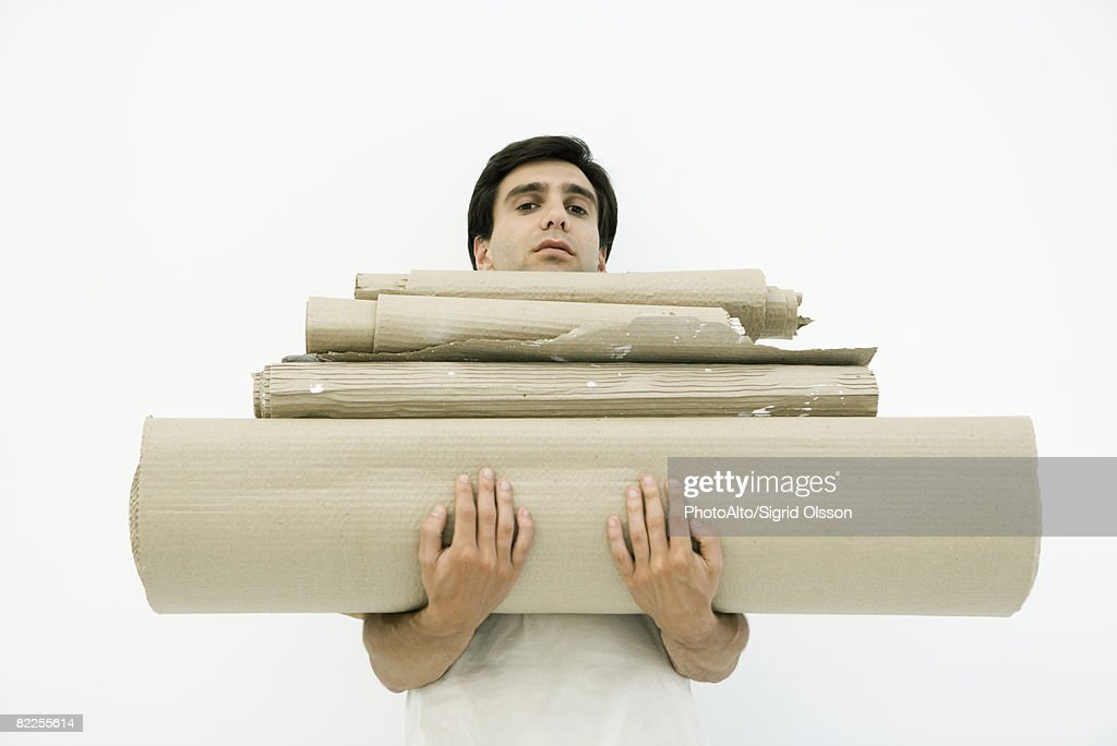 Man carrying large stack of corrugated cardboard, looking at camera : Stock Photo