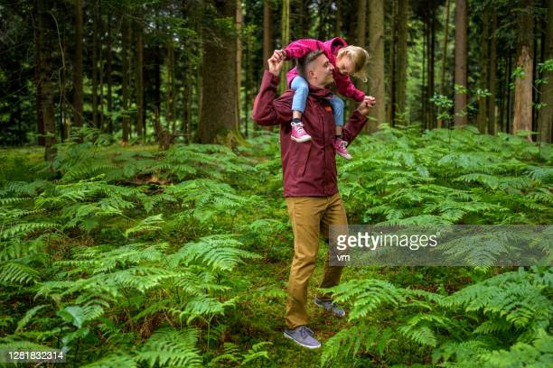 man carrying little girl on shoulders. - reality fernsehen stock pictures, royalty-free photos & images
