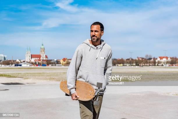 man carrying longboard outdoors - longboard skating stock-fotos und bilder