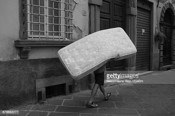 Man Carrying Mattress On Street