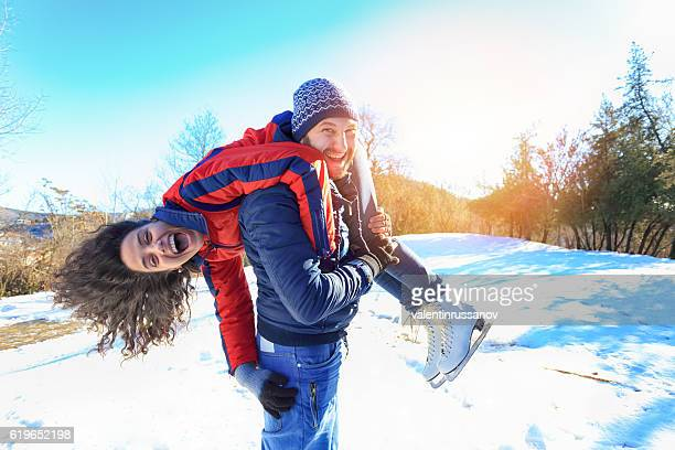 Man carrying on shoulder his girlfriend in the snow