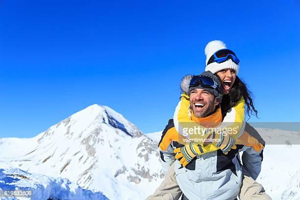 man carrying on shoulders his girlfriend on top snow mountain - cavalitas imagens e fotografias de stock
