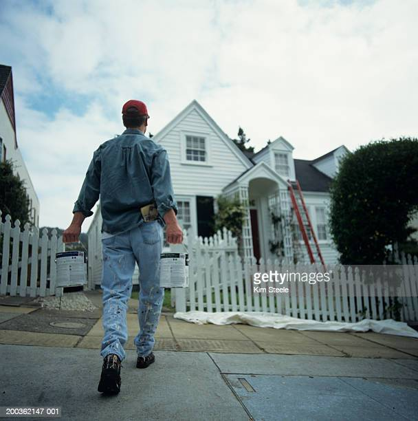 Man carrying paint tins walking towards house