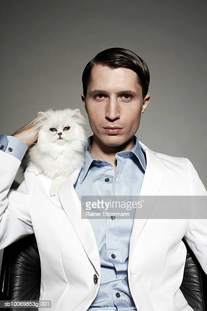 Man carrying Persian cat on shoulder, portrait, studio shot