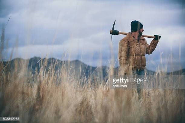 Man carrying pickaxe standing in hay field at dusk