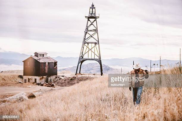 Man carrying pickaxe walking by old oil drill and barn