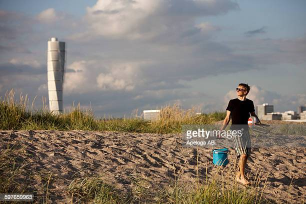 Man carrying picnic equipment at beach