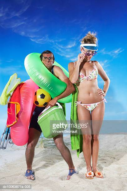 man carrying picnic objects on beach, woman standing besides - fat guy on beach stock pictures, royalty-free photos & images