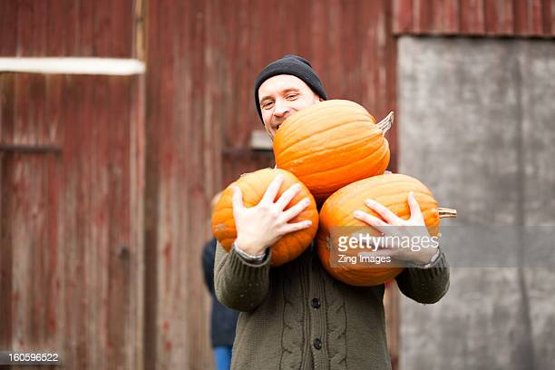 man carrying pumpkins - pumpkin stock pictures, royalty-free photos & images