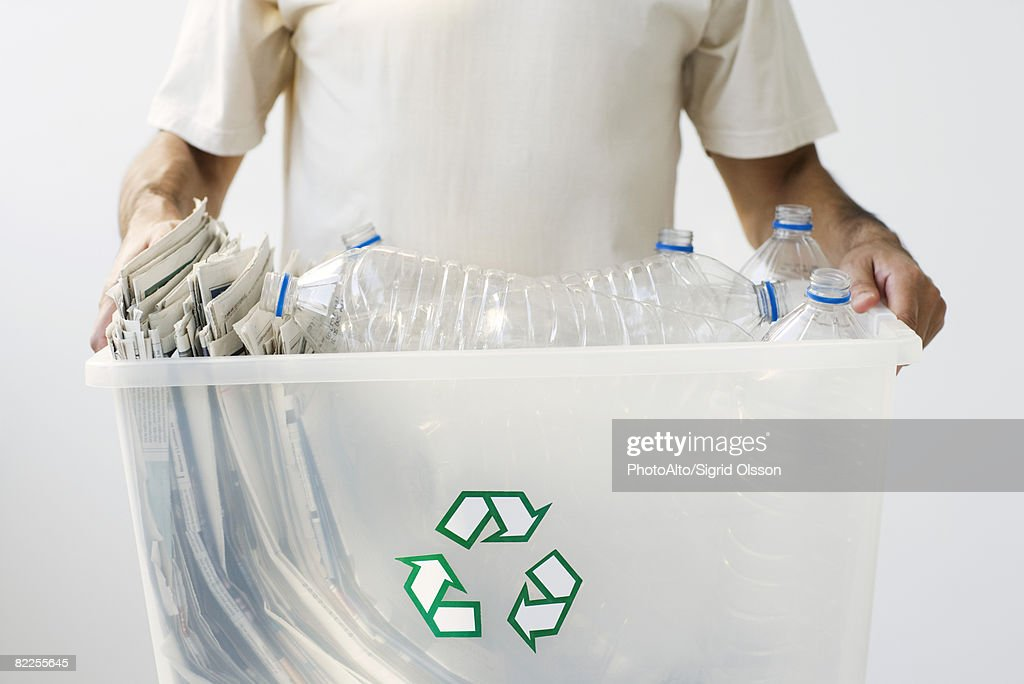 Man carrying recycling bin filled with plastic bottles and newspaper, cropped : Stock Photo