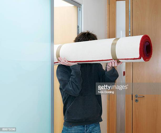 Man carrying rolled rug
