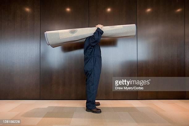 Man carrying rolled up carpet