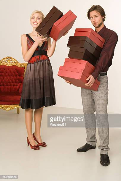 Man and woman carrying shoe boxes, portrait