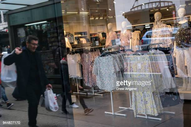 A man carrying shopping bags is reflected in a storefront window of an HM store in the Herald Square neighborhood of Manhattan April 11 2018 in New...