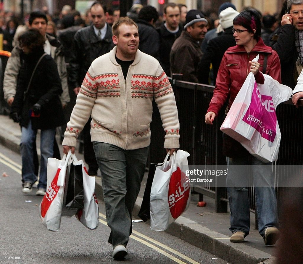 A man carrying shopping bags walks on the street becouse the pavement is too full of shoppers on Oxford Street on December 27, 2006 in London, England. With many stores open for the first time since Christmas Eve, bargain hunters are searching for the best buys as the post-Christmas sales get under way.