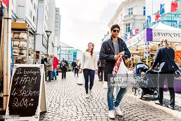 Man carrying shopping bags while walking with friends at market