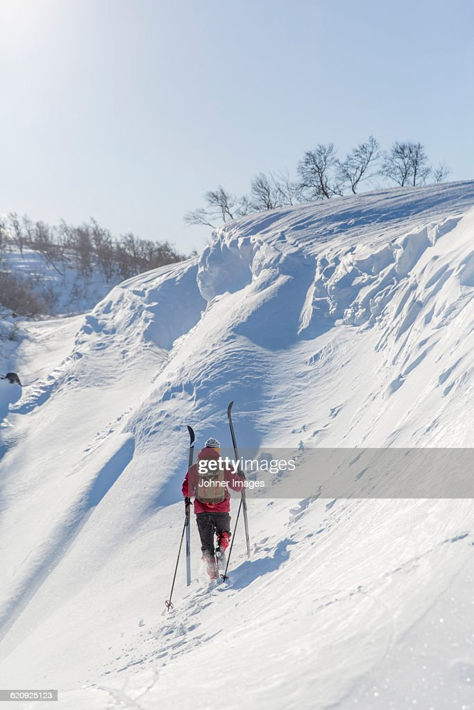 Man carrying skies up snowy slope : Stock Photo