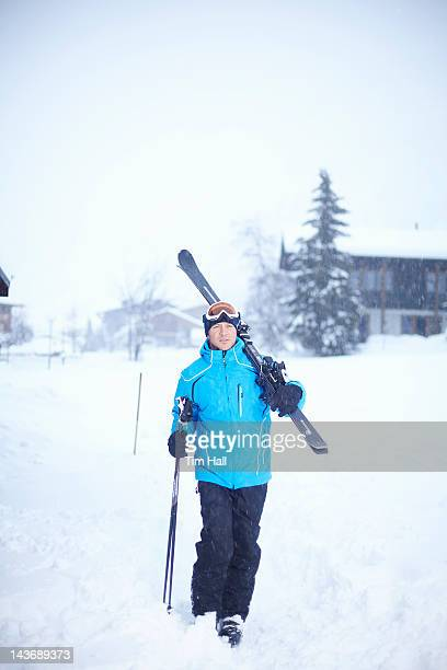 Man carrying skis and poles in snow