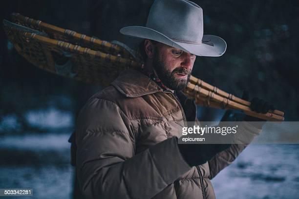 Mann am Telefon tragen Schneeschuhe aus und wandern bei Nacht