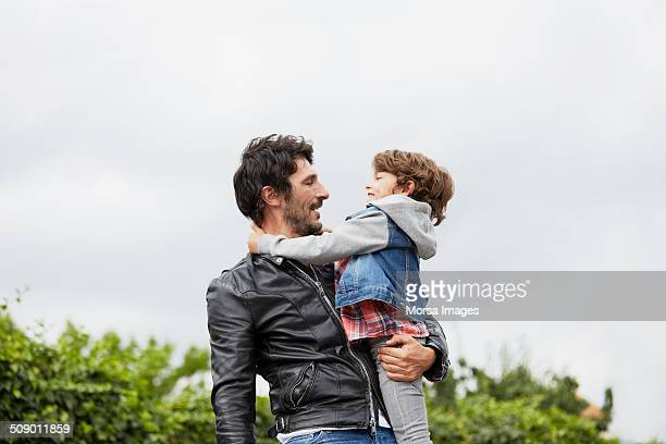 Man carrying son against clear sky