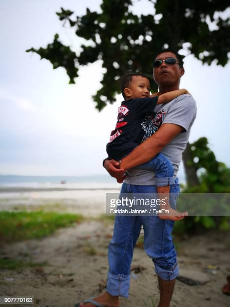 Man Carrying Son At Beach