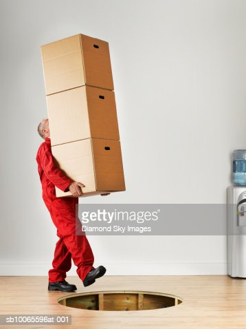 Man Carrying Stack Of Boxes Falling In Hole Of Wooden