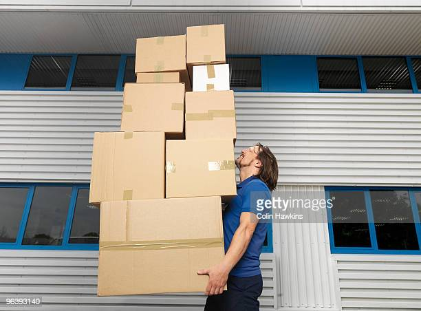 man carrying stack of boxes - excess stock photos and pictures