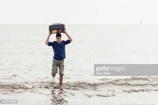 Man Carrying Suitcase Above Head And Exiting The Ocean